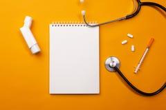 Stetoskop i doktorsskrivbord med anteckningsboken, inhalatorn och piller, bästa sikt arkivfoton