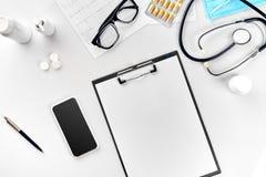 Stetoskop i kontoret av doktorer Bästa sikt av tabellen för skrivbord för doktors` s, tomt papper på skrivplattan med pennan kopi royaltyfri bild