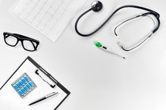Stetoskop i kontoret av doktorer Bästa sikt av tabellen för skrivbord för doktors` s, tomt papper på skrivplattan med pennan kopi arkivfoton