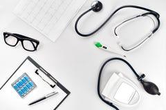 Stetoskop i kontoret av doktorer Bästa sikt av tabellen för skrivbord för doktors` s, tomt papper på skrivplattan med pennan kopi arkivbilder