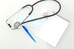 Stetoskop i kontoret av doktorer B?sta sikt av tabellen f?r skrivbord f?r doktors` s, tomt papper p? skrivplattan med pennan kopi arkivbilder