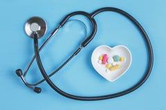 Stetoskop i różnorodne pigułki w spodeczku w kształcie serce na błękitnym drewnianym tle fotografia stock