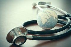 Stetoskop i tekstury kula ziemska z cyfrową pastylką Zdjęcie Royalty Free