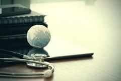 Stetoskop i tekstury kula ziemska z cyfrową pastylką Obrazy Stock