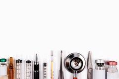 Stetoskop, injektionssprutor, sax, kirurgisk tång och ampuller Arkivfoton