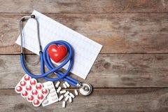 Stetoskop, kardiogram i pigułki na drewnianym tle, Kardiologii usługa Obrazy Stock