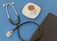 Stetoskop, kopp kaffe och tangentbord på en blå bakgrund stetoskop f?r pengar f?r begreppsliesmedicin set royaltyfri foto