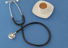 Stetoskop kopp kaffe på en blå bakgrund stetoskop f?r pengar f?r begreppsliesmedicin set arkivbild