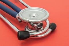 Stetoskop lub fonendoskop, z kawałkiem upwards dużą klatki piersiowej blendą lub, kłamający na up czerwonym jednolitym tła zakońc zdjęcia stock
