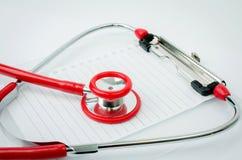 Stetoskop med den plast- skrivplattan, tomt papper Arkivfoton