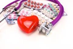 Stetoskop med preventivpillerar och röd hjärta som isoleras på vit bakgrund Fotografering för Bildbyråer
