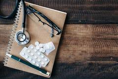 Stetoskop, medicin, droger, monokel och anteckningsbok på trätabellen royaltyfri fotografi
