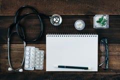 Stetoskop, medicin och anteckningsbok på trätabellbakgrund arkivbilder