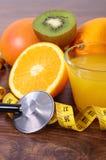 Stetoskop, nya frukter, fruktsaft och cm, sunda livsstilar och näring Arkivfoto