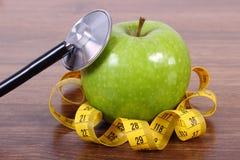 Stetoskop, nytt äpple och cm, sunda livsstilar och näring Fotografering för Bildbyråer