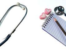 Stetoskop- och anteckningsbokrekord, vit bakgrund royaltyfri foto