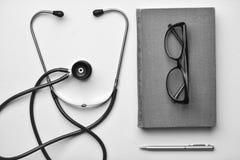 Stetoskop och bok på skrivbordet Royaltyfri Fotografi
