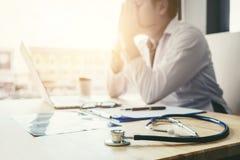 Stetoskop- och doktorssammanträde med bärbara datorn belastar huvudvärkabou Fotografering för Bildbyråer