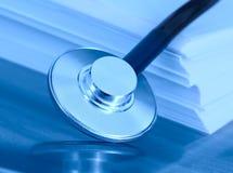 Stetoskop och en bunt av papper. Begreppet av den medicinska legislaen Arkivbilder