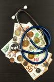 Stetoskop och giltiga tjeckiska sedlar för euro och Betald hälsovård Pengar som behandlar sjukdomen Arkivbilder