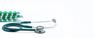 Stetoskop- och gräsplanpreventivpillerar i blåsapacken som isoleras på vit bakgrund med kopieringsutrymme Medicinskt hjälpmedel f Arkivfoto