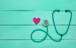 Stetoskop och hjärta på en blå trätabell Kardiologiutrustning för diagnostisering av kardiovaskulära sjukdomar Top beskådar arkivfoton