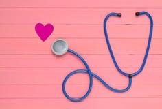 Stetoskop och hjärta på trätabellen för pastellfärgade rosa färger Kardiologiutrustning för diagnostisering av kardiovaskulära sj Royaltyfri Fotografi