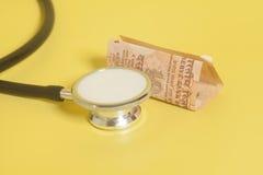 Stetoskop och indier 10 rupie anmärkningar på guling Arkivbild