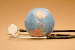 Stetoskop och jordklot Arkivbild