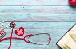Stetoskop och medicin för sjukvård- och läkarundersökningbegrepp röd på den blåa träbakgrunden fotografering för bildbyråer
