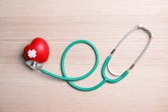 Stetoskop och röd hjärta med självhäftande murbrukar på träbakgrund, bästa sikt cardiology arkivbild