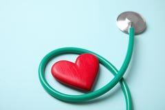 Stetoskop och röd hjärta på färgbakgrund cardiology arkivfoton