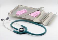 Stetoskop- och rosa färgpreventivpillerar på magasinet med exponeringsglas på isolerad whit royaltyfri foto