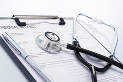 Stetoskop och sjukdomshistoria på reflexionsbakgrund Arkivfoton