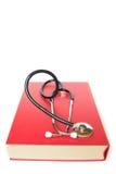 Stetoskop och stor röd bok Arkivfoto