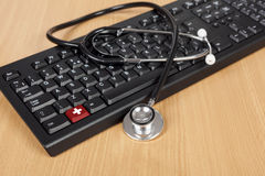 Stetoskop opuszczał drapuje nad komputerową klawiaturą na biurku Obraz Stock