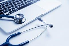 Stetoskop på bärbara datorn, sjukvård och medicin- eller datorantivirusskydd och begrepp för reparationsunderhållsservice royaltyfri bild