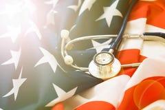 Stetoskop på bakgrunden av USA flaggan sjukförsäkringintrig nationellt vård- program arkivbild
