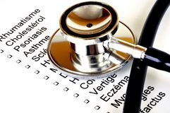 Stetoskop på en lista av sjukdomar som är skriftliga i franskt arkivfoto