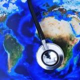Stetoskop på en världskarta (som möbleras av NASA) arkivfoton