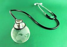 Stetoskop på ett crystal jordklot, begreppsmässig bild - grön bakgrund Arkivfoton