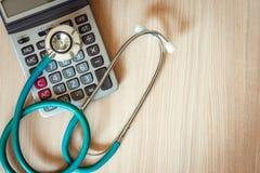 Stetoskop på räknemaskinen av för försäkringmeddelande för vård- undersökning begreppet , Medicinsk utrustning för affärssjukvård arkivbilder