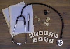 Stetoskop, pengar, penna med anteckningsboken och text: Hälsovård arkivbilder