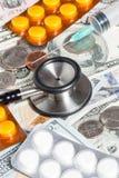 Stetoskop preventivpillerar, injektionsspruta över en bunt av dollar Royaltyfri Foto