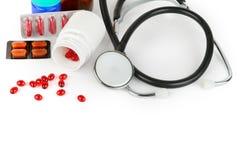 Stetoskop, preventivpillerar och läkarundersökningförberedelser som isoleras på vit bakgrund arkivbild