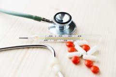 Stetoskop, preventivpillerar och termometer på trätabellen Medicin och Arkivfoto
