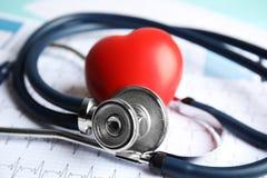 Stetoskop, röd hjärta och kardiogram på tabellen cardiology royaltyfria bilder