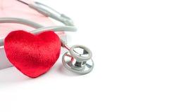 Stetoskop, röd hjärta och bok Arkivfoto