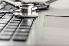 Stetoskop som ligger på ett bärbar datortangentbord Arkivbild