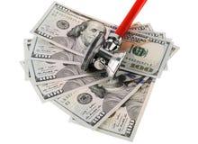 Stetoskop umieszcza na USA dolarów banknotach odizolowywających na bielu Fotografia Royalty Free
